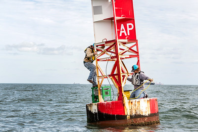 TAMU-CC Conrad Blucher Institute research engineers Zachary Hasdorff (left), and Alistair Lord attach prepare to tie a rope to the buoy during a CCPORTS module installation off of the coast of Port Aransas, Tx.
