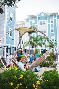Zain Khan, Ben Williams, and Jayde Harris relax pool side at Momentum Village.