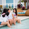 Students relax by the pool during Momentum Village's first day of spring pool party.