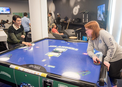 Emma Stimson (right) and Diego Vado (left) play air hockey in the Breakers Game Room