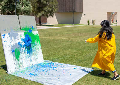 "Jasmine Ekunwe relieves some stress by throwing a paint filled balloon at a canvas during ""Paint Explosion"" on East Lawn."