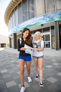 Yasmin Souza (left) and Hannah Stahl look over information packets provided by the Student Services Center.