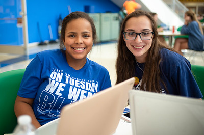 Brianna Roper (left) and Catherine Shaw multitask by working on their assignments in the UC Rotunda while watching performances at Islanders Got Talent.