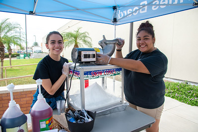 Sofia Rodriguez (left) and Savanah Araldua pose for photo as they prepare to serve free snowcones as a part of the All American Red, White and Blue Cook-Out at the UC Sea Breeze Patio