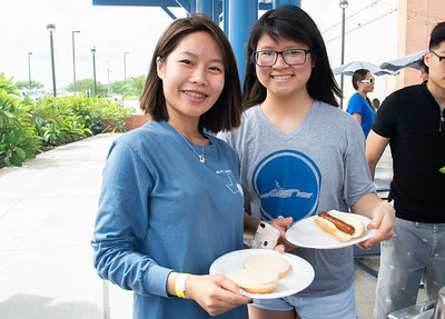 Huyen Bui (left) and Ngoc Do stop by after class at the UC Sea Breeze Patio for burgers and hotdogs in celebration for the right to peaceable assemble hosted by the UCP