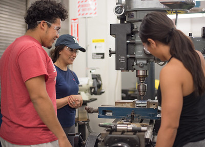 Students Pedro Galvan (left), Brittney Sauceda, and Tyanna Gold drill through aluminum pieces during Manufacturing Processes.