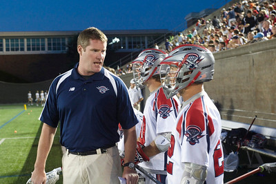 alumni lacrosse story:  Steve Duffy instructs a Boston Cannon player during a home game at Harvard University Stadium.