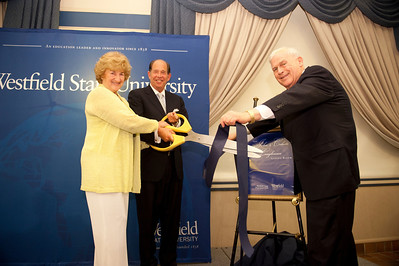 "(from left)  Doris Youmell, representing the Loughman Family, cuts the ribbon to celebrate the renaming of the Scanlon Living Room as the ""John and Celeste Lougman Living Room"" in honor of the Loughman's estate gift to Westfield State. President Evan Dobelle aids in the cutting, while Don Bowman, the executive director of the Westfield State Foundation holds the ribbon."