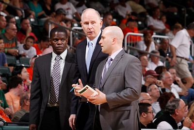 Chris Caputo confers with University of Miami head coach Jim Larranaga, middle, and assistant coach Michael Huger during a timeout. Photo by HurricaneSports.com