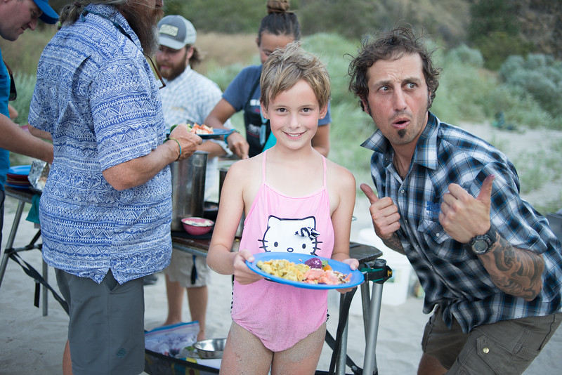 Salmon River Canyons, Idaho. Young girl and man posing with plate of food.