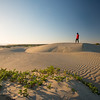 Woman standing on beach sand dunes.