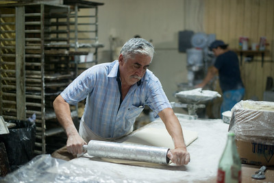 Mexico, Santa Rosalia. Panaderia El Boleo. Man slaving over dough.