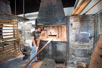Mexico, Santa Rosalia. Panaderia El Boleo. Man cooking on big oven.