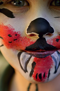 close up of a boy at a fete with face paint on to look like a little devil