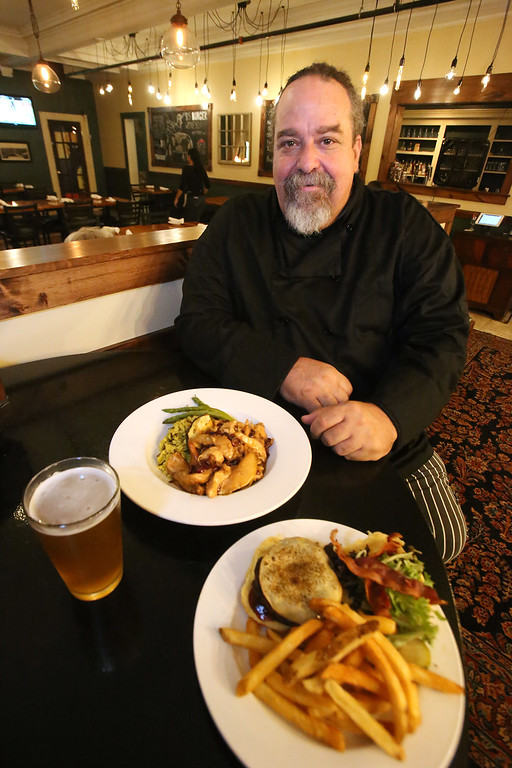 . Markoh\'s on Main restaurant in Ayer. Owner Markoh diCicco of Hollis, N.H., with the Smokehouse Burger, one of the burger options on $5 Burger Night, front, and Harvest Chicken (chicken with fresh sage, roasted butternut squash, apple cider reduction, and sometimes apples or pears, depending on what\'s good). (SUN/Julia Malakie)