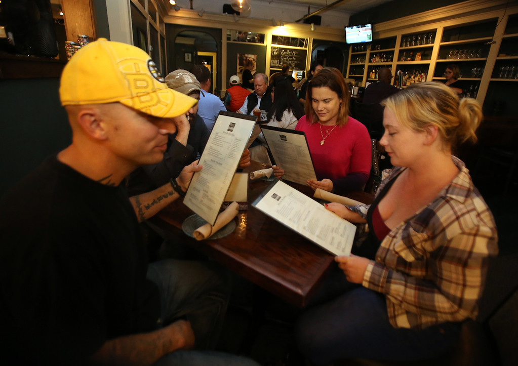 . Markoh\'s on Main restaurant in Ayer. Dan Donadio of Worcester, Tara Lyons of Ayer, rear, and Danielle Clarke of Worcester, look over the menu. (SUN/Julia Malakie)