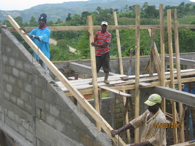 Presume Siporte in the blue shirt is the boss of the construction team and a member of the church.