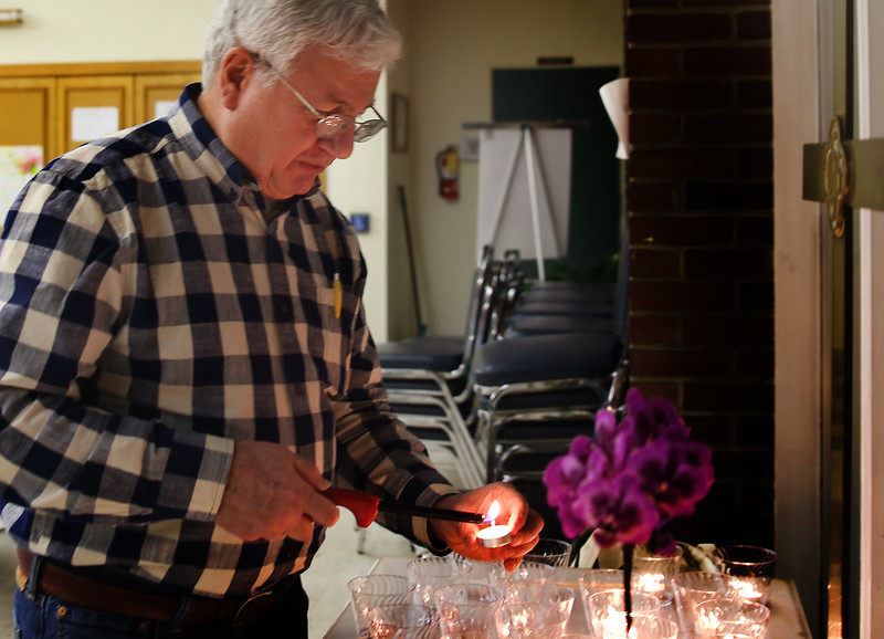 HOLLY PELCZYNSKI - BENNINGTON BANNER Claude Delucia, member of the Greater Bennington Peace and Justice Center lights candles to prepare for the Martin Luther King. Jr. Holiday Celebration candle light vigil on Monday evening in Bennington.