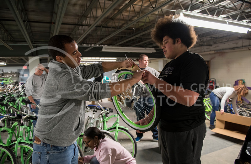 Two volunteers help each other unwrap one of the new Green Apple Bikes on Martin Luther King Jr. Day at the Green Apple Bike Warehouse in Manhattan, Kan., on Jan. 15, 2018. (Olivia Bergmeier | Collegian Media Group)