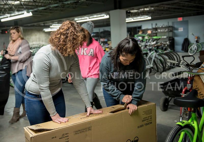 Two volunteers break down boxes from the new Green Apple Bikes on Martin Luther King Jr. Day at the Green Apple Warehouse in Manhattan, Kan., on Jan. 15, 2018. (Olivia Bergmeier | Collegian Media Group)