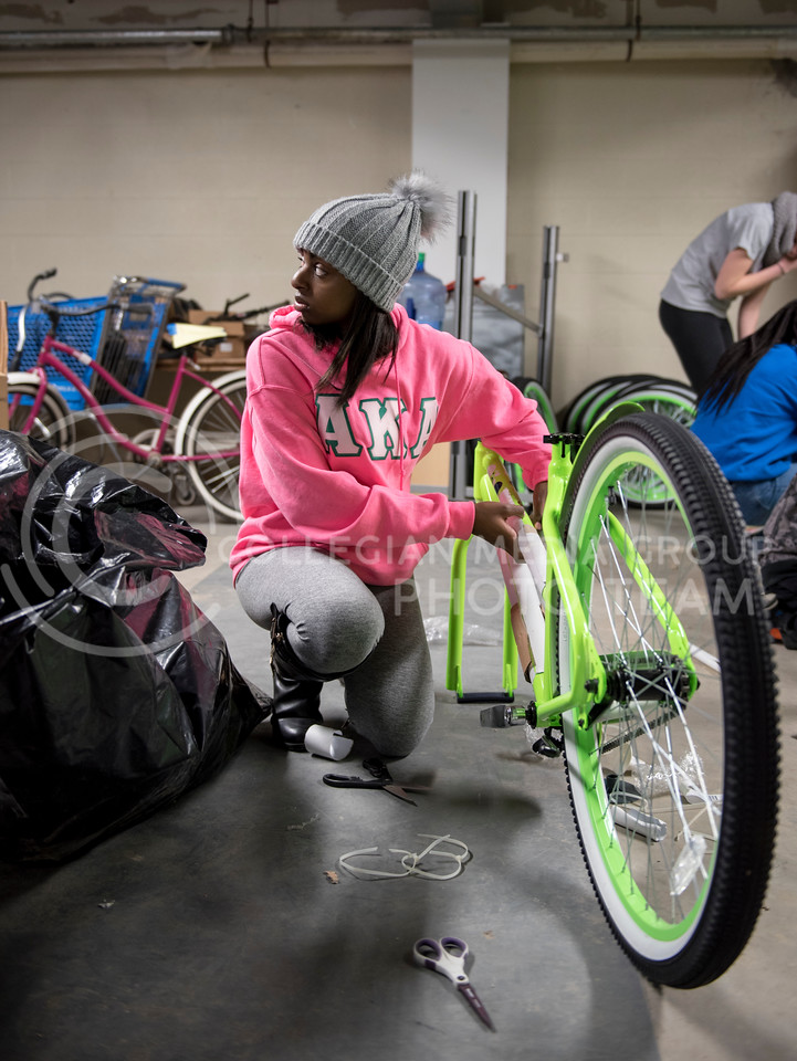 A volunteer helps unwrap one of the new Green Apple Bikes on Martin Luther King Jr. Day at the Green Apple Bike Warehouse in Manhattan, Kan., on Jan. 15, 2018. (Olivia Bergmeier | Collegian Media Group)