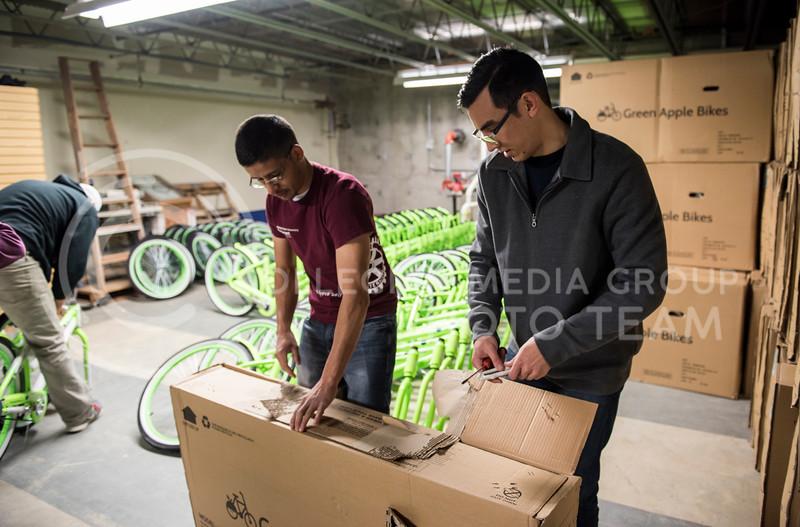 Two volunteers help unbox a new Green Apple Bike on Martin Luther King Jr. Day at the Green Apple Bike Warehouse in Manhattan, Kan., on Jan. 15, 2018. (Olivia Bergmeier | Collegian Media Group)