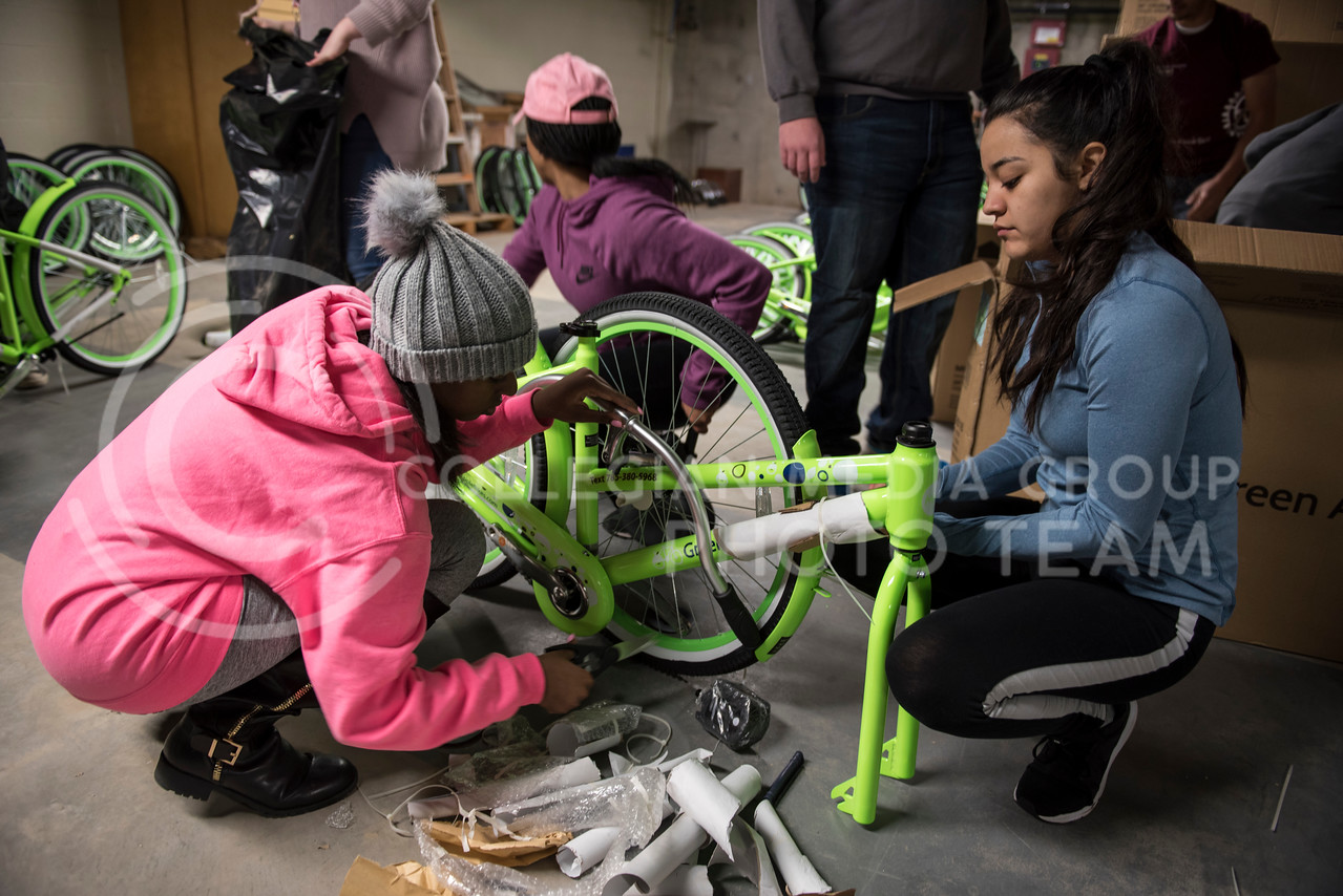 Community members help unbox the new Green Apple Bikes on Martin Luther King Jr. Day at the Green Apple Bike warehouse in Manhattan, Kan., on Jan. 15, 2018. (Olivia Bergmeier | Collegian Media Group)