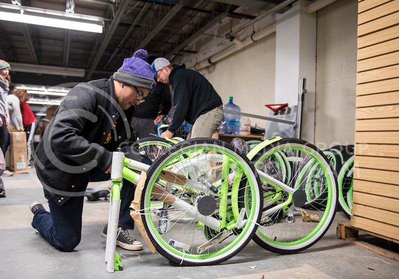 A volunteer helps unwrap a new Green Apple Bike on Martin Luther King Jr. Day at the Gree Apple Bike Warehouse in Manhattan, Kan., on Jan. 15, 2018. (Olivia Bergmeier | Collegian Media Group)