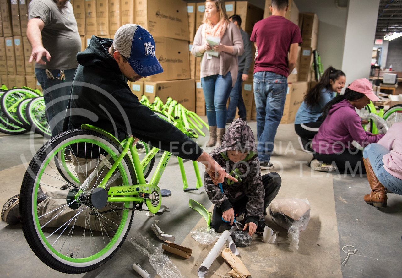 Community members come together on Martin Luther King Jr. Day to help unbox Green Apple Bike's brand new bikes in the Green Apple Warehouse in Manhattan, Kan., on Jan. 15, 2018. (Olivia Bergmeier | Collegian Media Group)