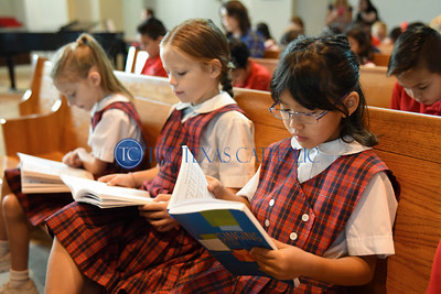 Michelle Kencono follows along in her choir book during a hymn at an all-school Mass August 30 at Mary Immaculate Catholic Church in celbration of the school's 60th anniversary. (Jenna Teter/Special Contributor)