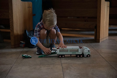 Cooper Mueller plays with his toy truck during an all-school Mass at Mary Immaculate Catholic Church August 30 to celebrate the 60the anniversary of Mary Immaculate Catholic School. (Jenna Teter/Special Contributor)