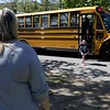 Mary Sirois waits for her adopted children Grace Sirois, 9, as she gets off the bus from school on Friday afternoon. Grace started out as one of her over 200 foster kid. SENTINEL & ENTERPRISE/JOHN LOVE