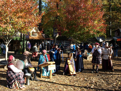 Musicians greet visitors to the little village in the woods.