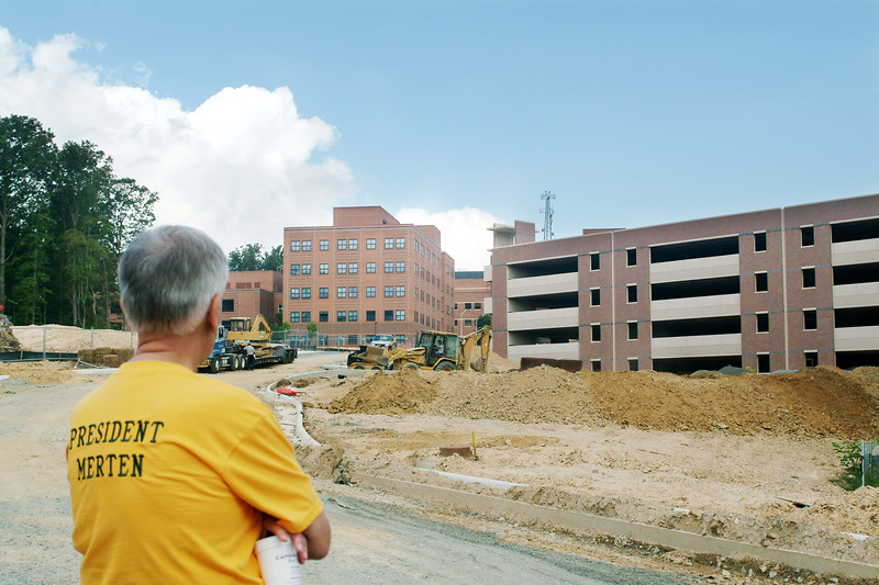 Dr. Merten taking a break from welcoming new students during move-in to check out the progress on construction at the site of today's Research Hall.