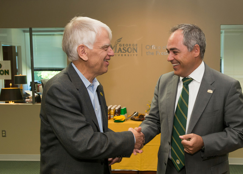 President Ángel Cabrera receives the keys to his office and the University from President Emeritus Alan Merten at Mason Hall on Fairfax Campus. Photo by Alexis Glenn/Creative Services/George Mason University