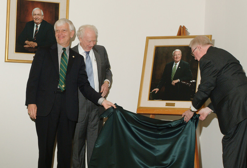 President Alan Merten and Sidney Dewberry unveil Edwin Meese's portrait during his final Board of Visitors meeting. Photo by Evan Cantwell.