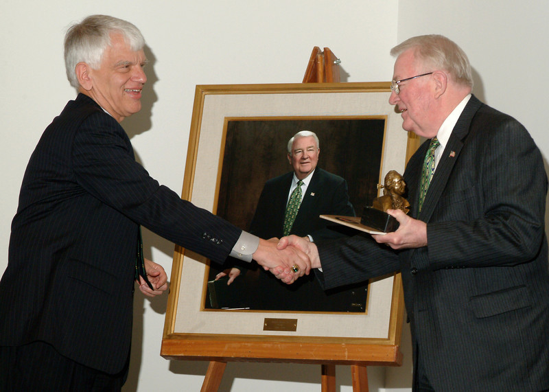 President Alan Merten and Edwin Meese shake hands after an unveiling of Meese's portrait during his final Board of Visitors meeting. Photo by Evan Cantwell.