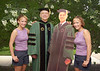 President Alan Merten poses with student twins wearing graduation regalia, 2001. Photo by Evan Cantwell/Creative Services