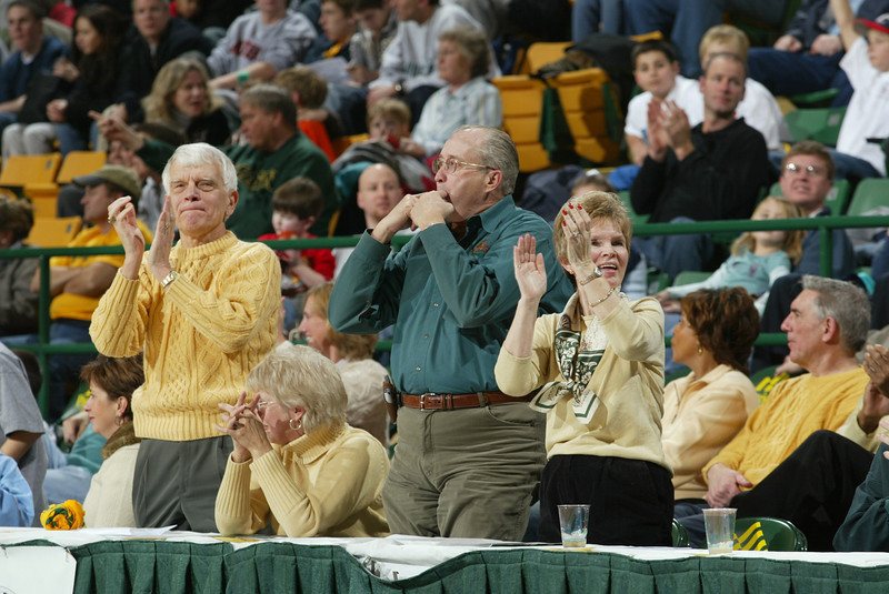 Dr. Merten, Dean Bill Reeder, and Sally Merten cheer on the Patriots at a men's basketball game.