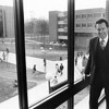 President George W. Johnson posing for a picture inside of Student Union Building I on the Fairfax Campus of George Mason University. Outside the window, the Fenwick Library Tower is the structure on the left and Robinson Hall A is the structure to the right. This picture was taken during Dr. Johnson's first academic year as university president on March 26, 1979. Photo courtesy of George Mason University