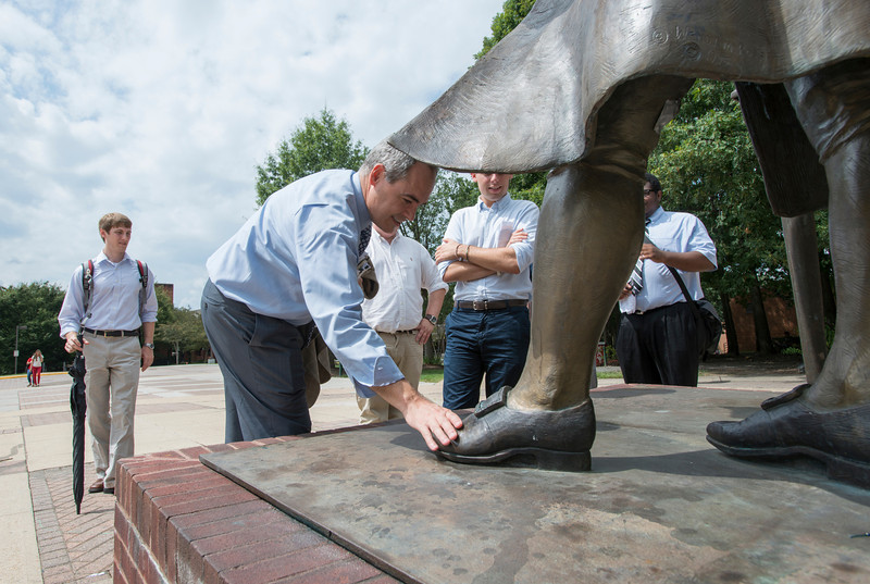 President Ángel Cabrera rubs the toe of the Mason Statue, a Mason tradition for good luck, as he tours Fairfax campus with students who participate in the Class Council Association and Student Government. Photo by Alexis Glenn/Creative Services/George Mason University