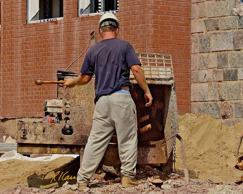 Masonry construction/mortar: Worker cleans mixer that produced mortar for laying rock wall. Mortar mixer has two main sections, the motor on left and the mixing drum on right. It can be towed, traveling on its two wheels behind a truck with trailer hitch. Masonry mortar is mixture of sand, portland cement or masonry cement, and water. At end of day mixer drum is coated with hardened mortar that must be cleaned off. The worker bangs outside of drum with small hand sledge hammer to break up mortar on inside surface of drum. He then rinses it out with water, checking it at end to be sure it is clean enough. Ann Arbor, Michigan 2005.