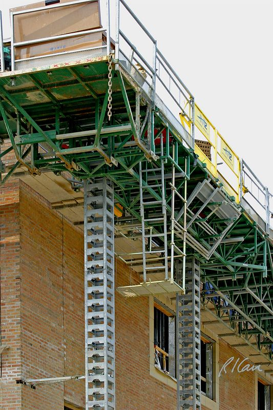 Hydro-Mobile modular mast-climbing work platform for laying brick. Masons lay brick standing on the 2x10 wood planks of the lower level, which is the left portion of the platform, against the building wall. Bricks and mortar are placed on the upper, material level, which is green in the photo. YMCA, Ann Arbor, 2004.