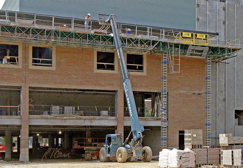 Brick construction: Gradall 534D9-45 rear pivot steering telescoping boom rough terrain material handler using forklift to place pallet of brick on masonry scaffold for vineer construction on third floor. YMCA, Ann Arbor, 2004.