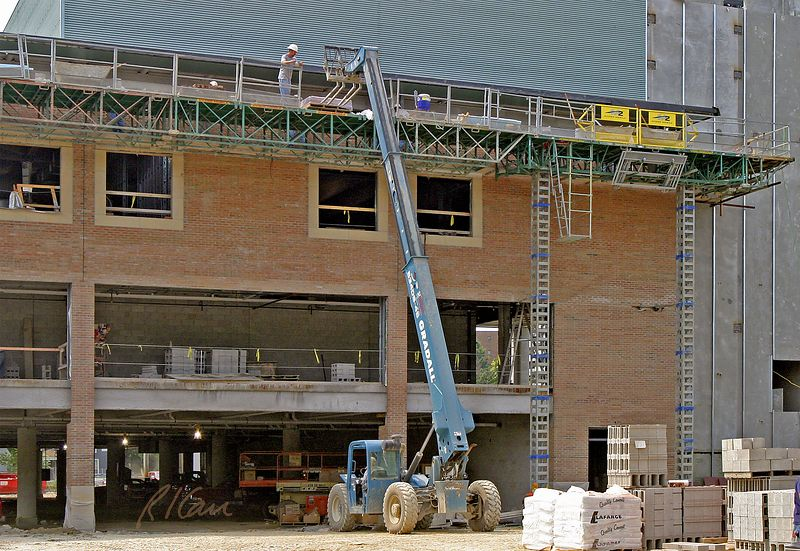 Brick construction: Gradall 534D9-45 rear pivot steering telescoping boom rough terrain material handler using forklift to place pallet of brick on masonry scaffold for vineer construction on third floor. YMCA, Ann Arbor, 2004.