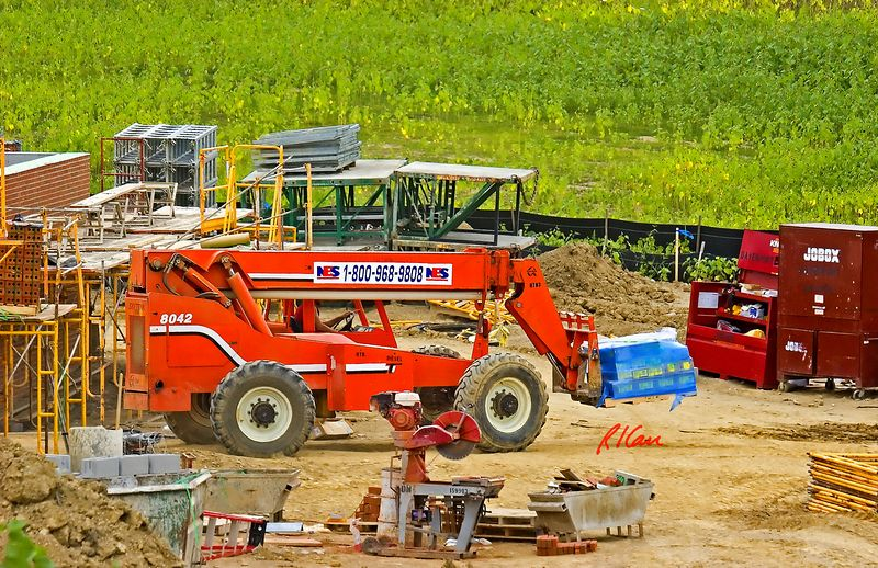 Masonry, brick, block, construction: SkyTrak 8042 4-wheel drive rough terrain hydraulic telescoping boom fork lift carries material on pallet. Rotary diamond blade saw station sits in front foreground. Scaffold storage is in rear and lower right. East Ann Arbor UMHS Clinic, Plymouth Rd, Ann Arbor, Michigan, 2005.