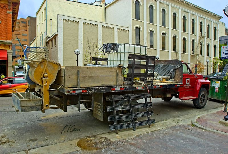 Masonry construction: Ford F700 flatbed truck outfitted as a rolling masonry constrkuction tender. Front of flatbed carries masonry units, middle section is large plastic water container, rear section holds masonryi cement, aggregate, and tools. Attached to rear is a top loading/dumping masonry mortar mixer, with mortar box. Williams Street between Main and Ashley, Ann Arbor, Michigan, 2005.