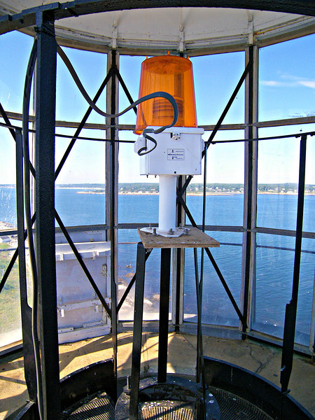 The current light exhibited by the North Tower is a 15 watt 250mm yellow light.  The light serves as a Private Aid to Navigation.  The yellow light is meant to recreate the oil light of the original 1771 tower.