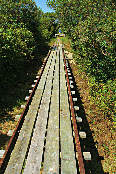 A narrow gauge railway was built to move supplies 900 feet across the island from the boathouse to the whistle house in 1888.  Extensions connecting the Keepers house to the Oil House were added later.  Handcarts were used to transport materials and the Thacher Island Association has one of the original carts.  The railway is also currently undergoing renovations.