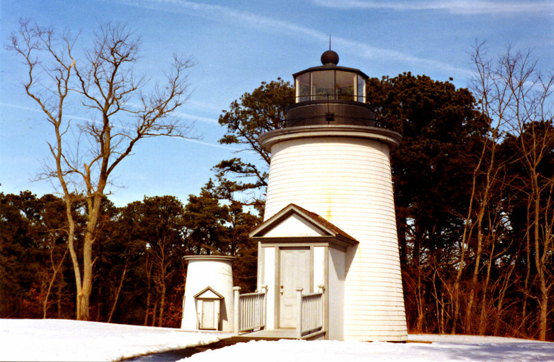 After an Assistant Keeper was assigned to the station in 1873, a new wood framed dwelling was added in 1876.  Over the years erosion ate away at the bluff bringing the towers closer to edge until in April 1892 three new wooden 22 foot towers were built thirty feet further away from the cliff.  The lanterns and lenses were moved to the new towers and later that year the brick towers toppled over the edge and down to the beach.
